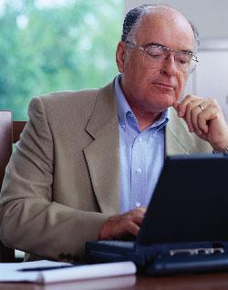 older man sitting at laptop